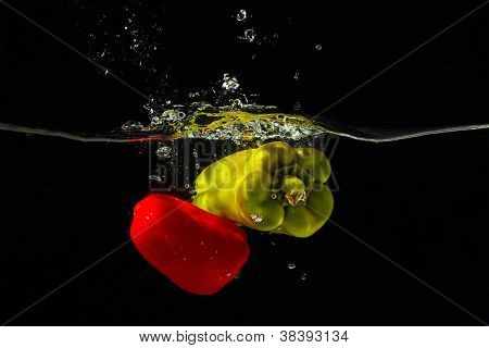 Fresh red and green bellpepper falling into the water with a splash on a black background