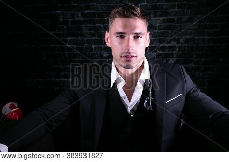 Portrait Of Handsome Man Wearing Tuxedo With Open Shirt Looking At Camera
