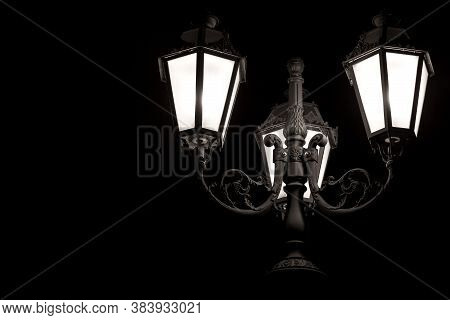 Black Forged Figured Iron Triple Retro Lantern With Frosted Glass Isolated On A Black Background Wit