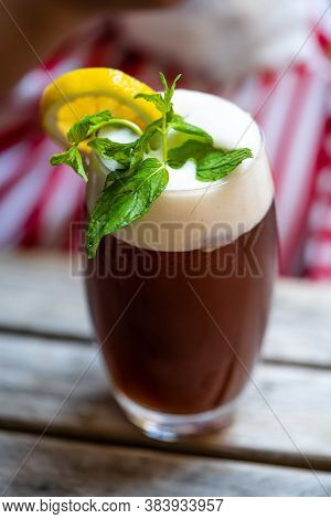 Foamy Iced Tea With Mint Leaves In Served With Big Glass / Ice Tea Foam On Wooden Table. Ready To Se