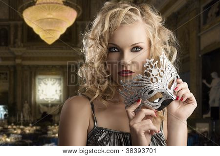 Blonde Girl Takes One Silver Mask With Both Hands