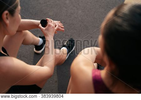 Women Tracking Time Using Arm Watch. Her Atractive Friend Waiting For Results.