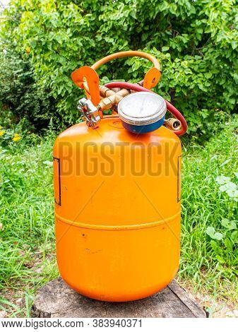 Refrigerant Cylinder And Hoses With Pressure Gauge. Orange Bottle With Freon. Pressure Gauge For The