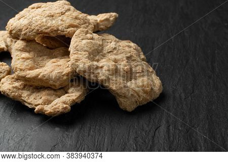 Raw Dehydrated Soy Meat Or Soya Chunks On Black Stone Background