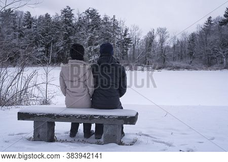 A Couple Sitting On A Snow Covered Bench Overlooking A Frozen Pond Within The White Memorial Conserv