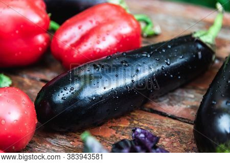 Bell Peppers And Eggplants Lie On A Wooden Surface. Concept Of Biological, Bio Products, Bio Ecology