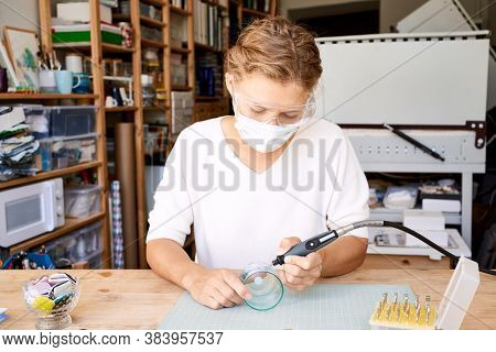 Female Entrepreneur In Face Protective Mask Burning Glass In Artisan Workroom. Business Woman