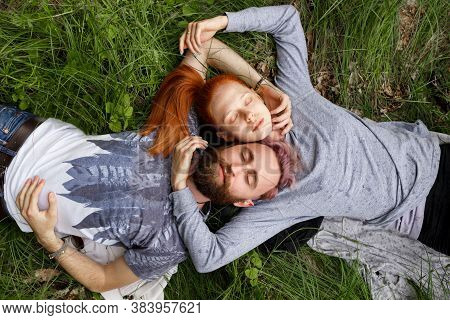 Top View Of A Couple, Seated Down On A Green Grass, Seated Down With Turned Heads With Closed Eyes.