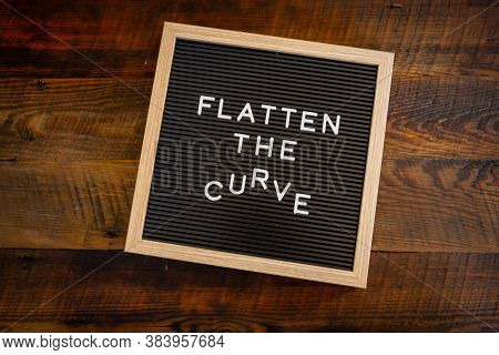 Flatten The Curving Curve Centered Over Wooden Background