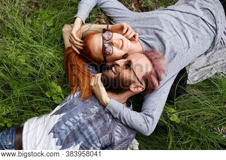 Top View Of A Beautiful Couple, Seated Down On A Grass, Seated Down With Turned Heads Wear In Sungla