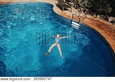 Cute Adorable Girl Floating On Back In Water Pool On Backyard. Kid Child Enjoying Having Fun In Swim