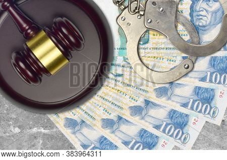 1000 Hungarian Forint Bills And Judge Hammer With Police Handcuffs On Court Desk. Concept Of Judicia