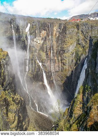 Beautiful Landscape. Waterfall Falls From A Cliff Into An Abyss And Small House On A Precipice. Norw