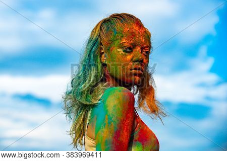 Portrait Of A Young Girl Painted In Color Powder. Color Face With Colorful Holi Splash. Beautiful Wo