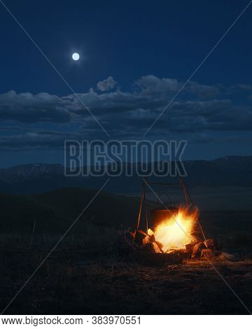 At Night On A Bonfire There Is A Bowler Hat, A Landscape Against The Background Of Mountains And The
