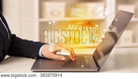 Side view of a business person working on laptop with AFFILIATE MARKETING inscription, modern business concept