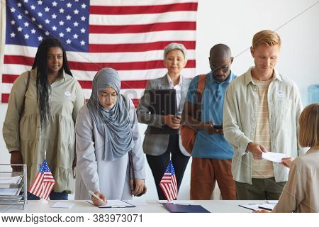 Multi-ethnic Group Of People Registering At Polling Station Decorated With American Flags On Electio