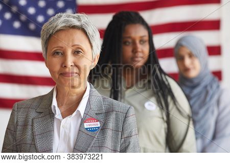Multi-ethnic Group Of People At Polling Station On Election Day, Focus On Smiling Senior Woman With