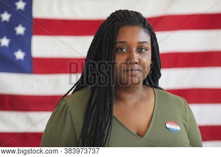 Head And Shoulders Portrait Of Young African-american Woman With Vote Sticker Looking At Camera Whil