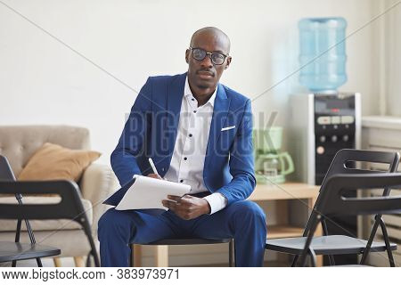 Portrait Of Elegant African-american Man Holding Clipboard And Looking At Camera While Sitting On Ch