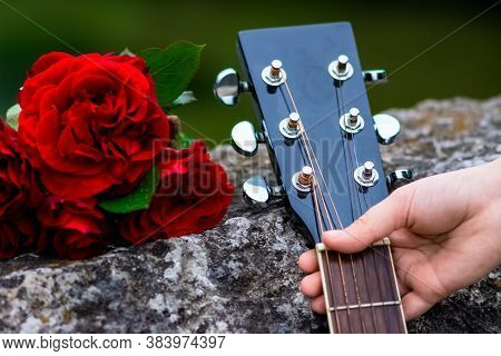 Acoustic Guitar Headstock And Bouquet Of Red Roses On The Old Bridge Wall. Girl Holding Neck In Her