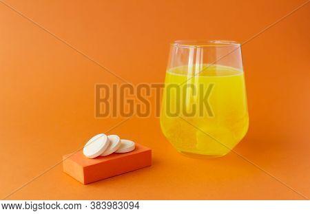 Effervescent Vitamins, Water-soluble Tablets On Orange Background.
