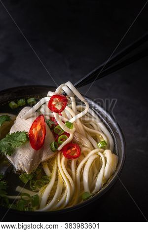 Close-up Of Spicy Asian Soup. Chicken Bouillon And Meat, Red Chilli Pepper, Cilantro, Scallions, Jap