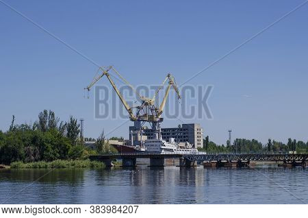 View From The Shore To The Shipyard. Two Harbor Cranes And A Ship Under Repair At The Berth. A Shipy