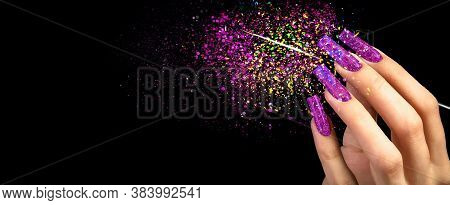Hand With Bright Manicure And A Brush On A Black Background Strewn With Sparkles. Nail Design. Exten
