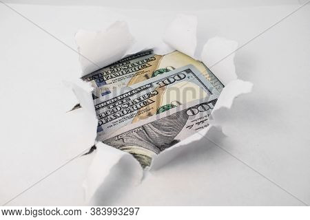 The White Paper Is Torn In The Center Inside The Hole Is A Background Of Dollars. The Concept Of A B