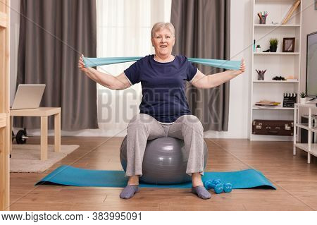 Aged Woman Enjoying Exercise In Her Cozy Apartment. Old Person Pensioner Online Internet Exercise Tr