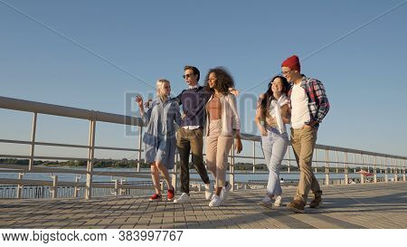 Diverse Young Smiling Friends Walking On Warm Day, Having Fun To