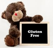 A brown bear holding a gluten free chalkboard poster