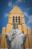 Statue of Jesus Christ in front of St. Willibrordus church in Curacao, Netherlands Antilles. Sint Willibrordus Roman Catholic church was built between 1884 and 1888 in the Neo-Gothic architectural style common for churches built in that period. poster