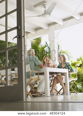 Low angle view of three middle aged people sitting at verandah table