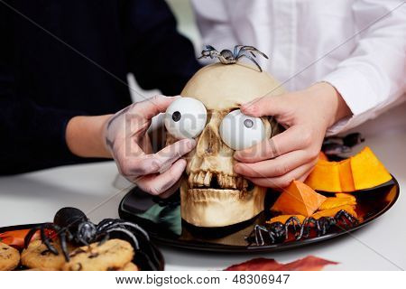 Photo of two boys hands holding spooky eyes just in skull eye-sockets