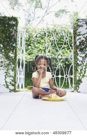 Full length of little girl having breakfast on porch
