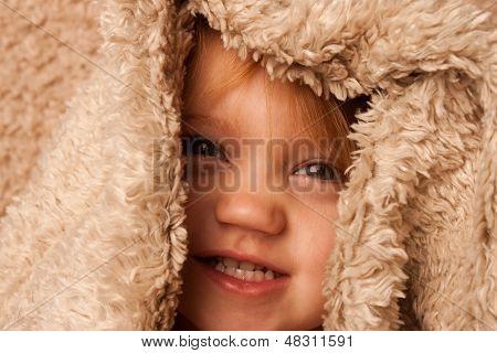 Smiling toddler hiding in fur blanket