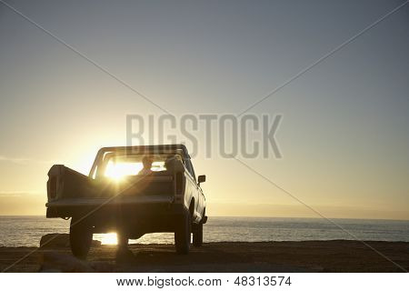 Rear view of young couple in pick-up truck parked in front of ocean enjoying sunset poster