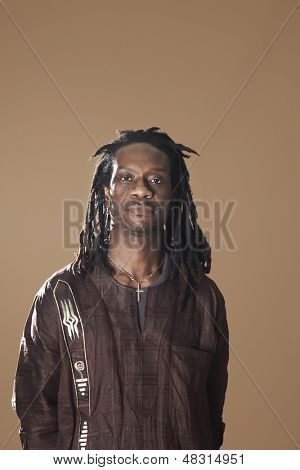 Portrait of African American man with dreadlocks standing on brown background
