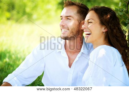 Happy Couple Outdoor. Smiling Couple Relaxing in a Park. Family over Nature Green Background. Smiling Man and Woman Having Picnic in Countryside. Relationships