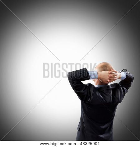 Back view image of businessman with arms crossed behind head. Place for text