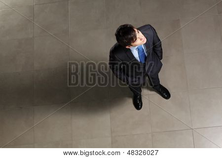 Image of young businessman looking above. Top view
