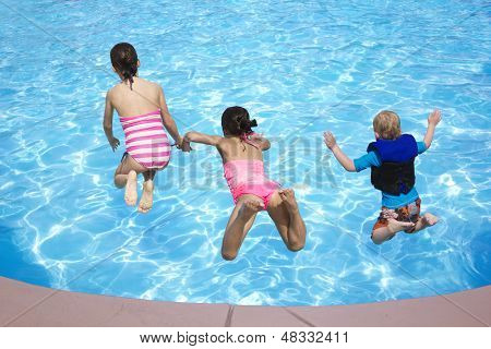 Three Kids jumping into the Swimming Pool