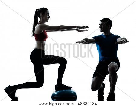 personal trainer man coach and woman exercising squats on bosu silhouette  studio isolated on white background poster
