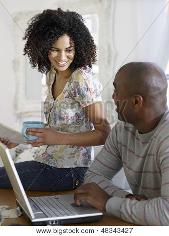 African American couple sitting at table with laptop and bills