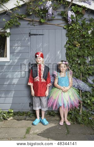 Full length portrait of a young boy in pirate costume and girl in fairy costume by shed