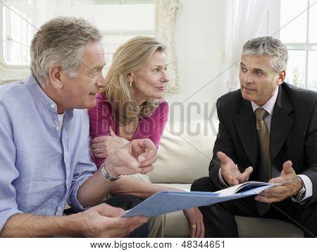 Älteres Paar sitzt auf Sofa mit Finanzberater