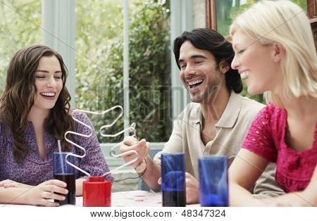 Cheerful young multiethnic friends sitting at verandah table