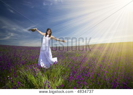 Beautiful Young Woman With White Dress In Flower Field